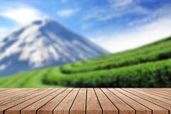 Pavimento di legno con bello paesaggio vago della piantagione di tè Immagini Stock