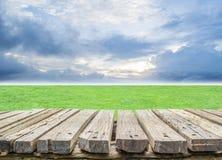 Pavimento di legno con il campo di erba Fotografie Stock
