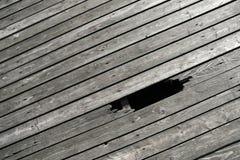 Pavimento di legno con il foro della rottura fotografia stock