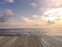 Pavimento di legno con luce della spiaggia di tramonto, bello cielo, tramonto nel mare Immagine Stock