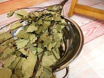 Pavimento di legno della sauna con il mazzo della betulla in ciotola del metallo Sauna tradizionale finlandese o russa fotografia stock libera da diritti