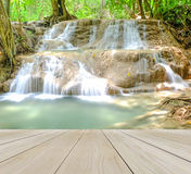 Pavimento di legno di prospettiva con la cascata nella foresta affinchè uso Relax deridano su Fotografia Stock