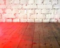Pavimento di legno nero e fondo bianco del muro di mattoni Copi lo spazio con l'alone della luce del sole modificato Fotografie Stock