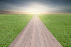 Pavimento di legno sul fondo di tramonto del cielo e dell'erba verde Immagine Stock Libera da Diritti