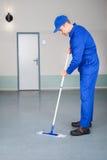 Pavimento di pulizia del lavoratore Immagine Stock
