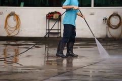 Pavimento di pulizia del lavoratore con il fondo della macchina di alta pressione dell'aria Fotografie Stock