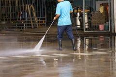 Pavimento di pulizia del lavoratore con il fondo della macchina di alta pressione dell'aria Fotografia Stock Libera da Diritti