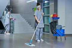 Pavimento di pulizia del lavoratore con la macchina Immagini Stock