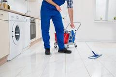 Pavimento di pulizia del lavoratore nella stanza della cucina Fotografie Stock Libere da Diritti