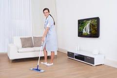 Pavimento di pulizia della domestica con la zazzera Fotografia Stock Libera da Diritti
