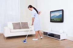 Pavimento di pulizia della domestica con la zazzera Immagine Stock Libera da Diritti