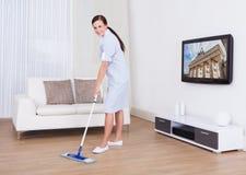 Pavimento di pulizia della domestica con la zazzera Immagini Stock Libere da Diritti