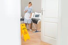 Pavimento di pulizia della domestica con la zazzera Fotografie Stock Libere da Diritti