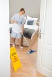 Pavimento di pulizia della domestica con la zazzera fotografia stock