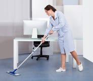 Pavimento di pulizia della domestica in ufficio immagine stock