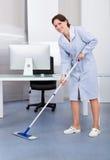 Pavimento di pulizia della domestica in ufficio immagini stock