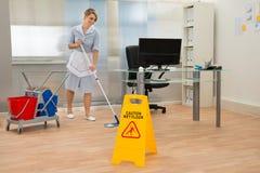 Pavimento di pulizia della domestica in ufficio fotografie stock