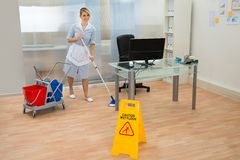 Pavimento di pulizia della domestica in ufficio Immagine Stock Libera da Diritti