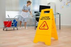 Pavimento di pulizia della domestica in ufficio Immagini Stock Libere da Diritti