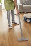 Pavimento di pulizia della donna con un aspirapolvere nella sala Fotografie Stock