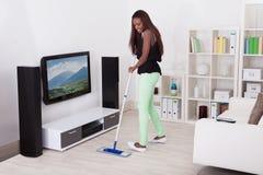 Pavimento di pulizia della donna in salone Fotografia Stock Libera da Diritti