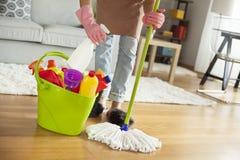 Pavimento di pulizia della giovane donna nella sala Immagine Stock