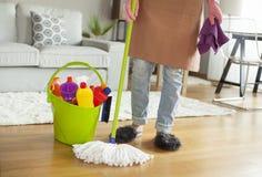 Pavimento di pulizia della giovane donna nella sala Fotografia Stock