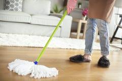 Pavimento di pulizia della giovane donna nella sala Immagine Stock Libera da Diritti