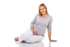 Pavimento di seduta della donna incinta fotografia stock libera da diritti