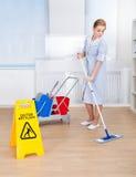 Pavimento felice di pulizia della domestica con la zazzera Fotografia Stock Libera da Diritti