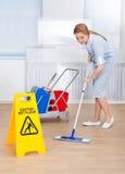 Pavimento felice di pulizia della domestica con la zazzera Fotografia Stock