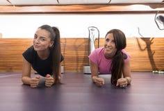 Pavimento felice sorridente della plancia di forma fisica di due donne Immagini Stock Libere da Diritti