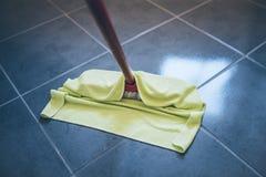 Pavimento piastrellato di pulitura umido con il panno di pulizia del pavimento immagine stock