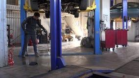 Pavimento sporco pulito del tipo del lavoratore sotto l'automobile d'attaccatura nel garage di riparazione archivi video