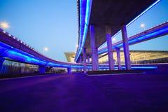 Pavimento vuoto della strada con il ponte del viadotto della città della notte delle luci al neon Fotografia Stock Libera da Diritti