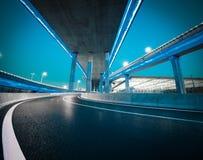 Pavimento vuoto della strada con il ponte del viadotto della citt? della notte delle luci al neon fotografia stock libera da diritti