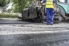 Paving applicator machine or paver with worker. Work on the laying of asphalt in the city. Paving applicator machine or paver with worker Stock Photos