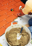 Paving the floor of the terrace of a house with ceramic tile Stock Photos