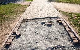 Paving the footpath with the tiled cubes. Royalty Free Stock Photos