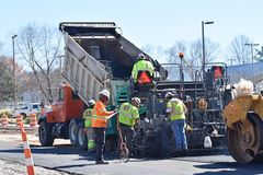 Paving machine and crew on highway project. A paving machine and crew on a highway improvement project near Greenville SC/USA are shown. Steam can be seen rising Royalty Free Stock Photos