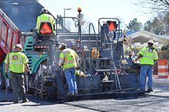 Paving machine and crew on highway project. A paving machine and crew on a highway improvement project near Greenville SC/USA are shown. Steam can be seen rising Royalty Free Stock Photography