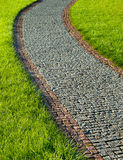 Paving the path from granite stones in green grass Stock Photo