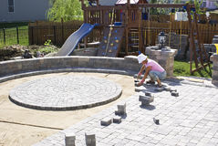 Paving the Patio. Woman with the white hat paving patio at the backyard of their house Stock Image