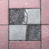 Paving slabs with symmetrical hollows, filled with small stones bluish and reddish color. Geometric shape resembling the squares of a chessboard Royalty Free Stock Photo