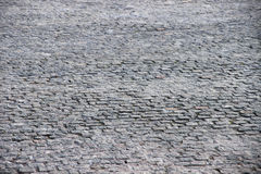 Paving stone. Stone road paved with cobblestones royalty free stock image