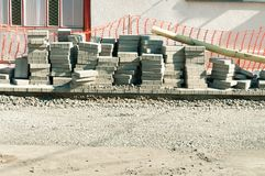 Paving stone tiles prepared to pave over gravel road on the street reconstruction site. Royalty Free Stock Photo