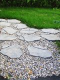 Paving stones. Uneven paving stone, pebbles and grass Royalty Free Stock Photos