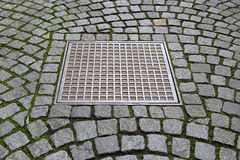 Paving stones with metal manhole Stock Photos
