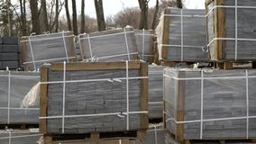 Paving stones packed in stacks and wrapped in film are stored on ground outdoors. Landscape design, improvement of cityscape and city planning. construction stock video