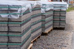 Paving stones on several pallets, covered with foil as rain protection Stock Images